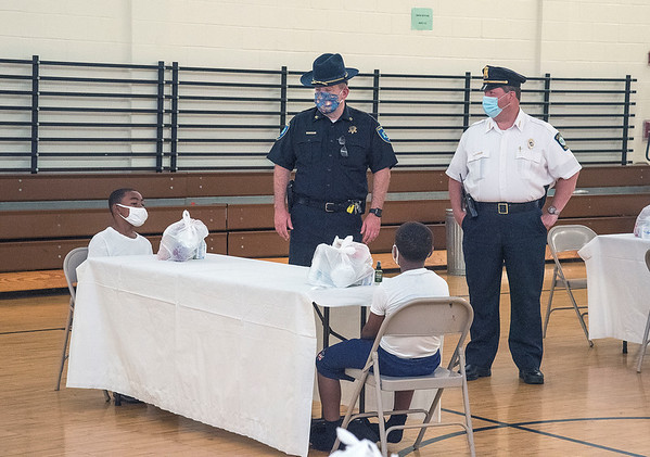 200727 Building Bridges 2<br /> James Neiss/staff photographer <br /> Niagara Falls, NY - Niagara County Sheriff Michael Filicetti and Niagara Falls Police Superintendent Thomas Licata chat with children in the Building Bridges Program at the Packard Court Community Center. <br /> <br /> Niagara Falls Mayor Robet Restino kicks off the Building Bridges Program at the Packard Court Community Center. The City of Niagara Falls in partnership with the Niagara Falls Police Department and Niagara County Sheriff's Department started the program to help foster relationships between children from the inner city. Approximately 20 children, between the ages of 8 and 12 years old, will be visiting local attractions such as Niagara Falls Cave of the Winds, the Aquarium of Niagara, Confer Plastics, and more while being granted the opportunity to positively interact with local police officers and sheriff deputies. This program runs Monday, Wednesday, and Friday, from 11 am to 3 pm, starting Monday, July 27th, and concluding on Friday, August 7th.