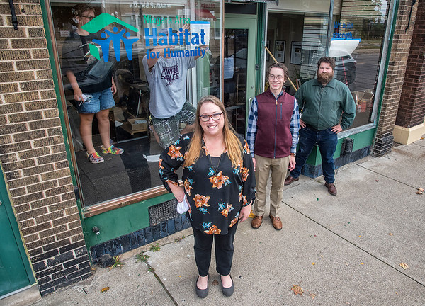 201012 Niagara Habitat 1<br /> James Neiss/staff photographer <br /> Niagara Falls, NY - The Niagara Area Habitat for Humanity relocated its office to 1221 Main Street with staff, from left, Gina Beam, executive director, Marco Notaro, community outreach director and Ben Lee, Americorp Vista member. Working on the signage is Ginas husband Michael Beam.