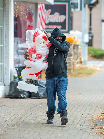 "201118 Enterprise 1<br /> James Neiss/staff photographer <br /> Lewiston, NY - A time for every season - Damon ""13"" Harvey of Buffalo was spotted happily carrying a giant plastic Santa to his car. The Santa was the last item available at Sister & Brother Children's Apparel in Lewiston as they closed their doors for good after opening in 1954."