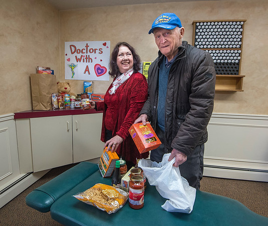 "James Neiss/staff photographer <br /> Lewiston, NY - Dr. Glenda Rose accepts a food donation from patient Edwin Torba of Youngstown who came to her chiropractic office for an adjustment. Rose Chiropractic is participating in the 30th Annual Doctors with a Heart Day.<br /> <br /> ""30th ANNUAL DOCTORS WITH A HEART DAY""<br /> On Saturday, February 8, 2020 from 9am - 12pm, Dr. Glenda R. Rose and Dr. Thomas G. Barba of Rose Chiropractic, P.C. in Lewiston will be sponsoring the 30th Annual ""Doctors with a Heart Day"" for their patients. Non-perishable food items will be collected to benefit the Niagara Community Action Program (NiaCAP) food pantry in exchange for chiropractic services.<br /> The Public is welcome to participate the week before and the week after the event: February 3th – 15th. For a bag of non-perishable food you will receive a chiropractic or Nutrition Response Testing exam & consultation to find out how you can improve your health naturally. Rose Chiropractic, P.C. is located at 435 Ridge St., in Lewiston. Call 754-9039.<br /> A limited number of appointments are available."