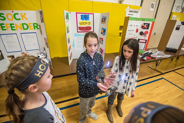 James Neiss/staff photographer <br /> Lockport, NY - Students Allison Reynolds and Abigail Williams show off The Book Holder, an invention that not only illuminates the printed pages of a book, but has special clips that keep the pages from turning.