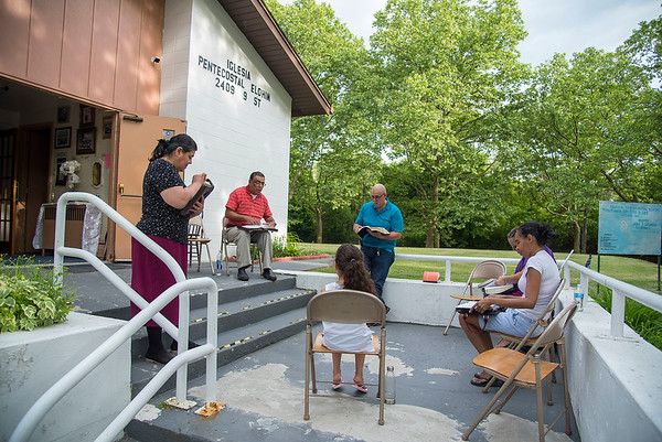 2006018 Enterprise 4<br /> James Neiss/staff photographer <br /> Niagara Falls, NY - Pastor Jose Quinones, second from left, reads from the bible during an outdoor spanish speaking bible study at the Iglesia Pentecostal Elohim church on 9th Street. Joining him from left are his wife Lourdes Quinones and parishioners Geraldo Rivera, Mary Rivera, Ires Crespo and Miaelis Crespo. The bible study theme this week was Sanctification, how you can live in the holy spirit. The group meets every Tuesday and Thursday at 6 p.m. and all are welcome and there is an english interpreter.