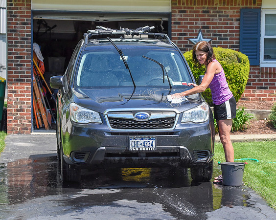 200526 Lkpt Enterprise 1<br /> James Neiss/staff photographer <br /> Lockport, NY - Kate McCarthy of Sandy Lane didn't seem to care at all about the midday heat as she washes the bugs and dirt off her car.