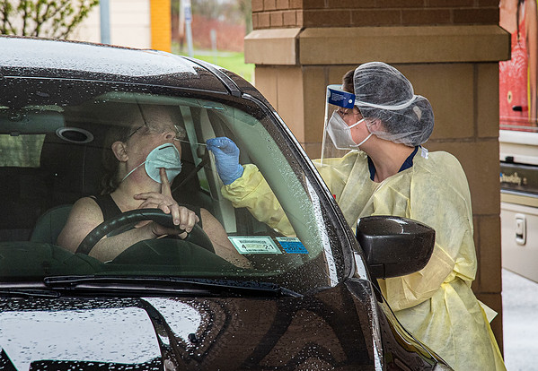 200430 COVID Testing 1<br /> James Neiss/staff photographer <br /> Niagara Falls, NY - Nurse Practitioner Emily LaDuca takes a sample from Cindy McDonough of Niagara Falls at the Community Health Center of Niagara to test it for COVID-19. The Community Health Center of Niagara medical mobile unit will be available for drive-up and walk-up testing at 2715 Highland Avenue. Call 716-989-9199, option 9, to schedule a COVID-19 diagnostic test.