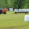 200528 Enterprise 2<br /> James Neiss/staff photographer <br /> Gasport, NY - Getting It Done - A farmer gathers bails from a field off Gill Road in Gasport.