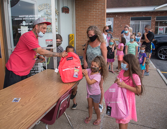 "200901 Backpack Giveaway 1<br /> James Neiss/staff photographer <br /> Lockport, NY - Zoeey Molina, 5, left, and sister Alainah Allinson, 8, received backpacks filled with school supplies from Toys by LO owner Joshua Lopez, as many others line up behind.<br />  <br />  <br /> Toys by LO, 32 Main St. Lockport NY 14094<br /> Description:<br /> 200 filled backpacks, all ""raised"" through donations by Toys by LO operator Joshua Lopez and barber Josh Pagan, are being distributed at Toys by LO beginning at 7 p.m. First come, first served. Lopez put out the word previously that anyone who NEEDS stuff — not wants, needs — is welcome."