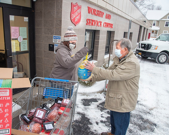 201217 Salvation Army 1<br /> James Neiss/staff photographer <br /> Lockport - Volunteers Ed Sandusky and Angellica Bryan gather food to distribute to families in need for the Lockport Salvation Army's Christmas assistance program. Over 130 families have applied and qualified for the program. Food items include chicken, turkey and ham, as well as toys for children.