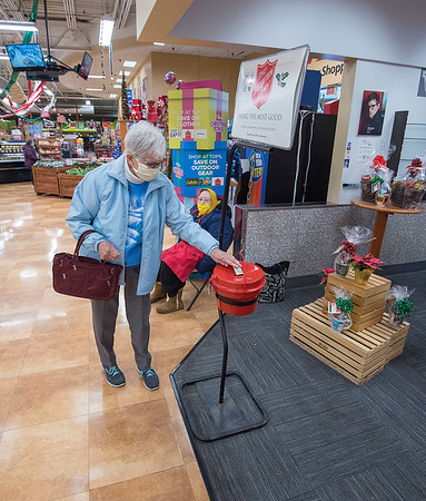 201203 Bell Ringer Enterprise 2<br /> James Neiss/staff photographer <br /> Lockport, NY - Lockport Salvation Army bell ringer Dorothy Camman watches as Rachel Schafsteck of Lockport makes a kettle donation at Tops.