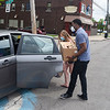 200529 Food Giveaway 1<br /> James Neiss/staff photographer <br /> Niagara Falls, NY - Schoolboard member Earl Bass carries a box of food to the car of Emily Schumacker, part of a program sponsored by the Cornell Cooperative Extension of Niagara and the USDA. Participants each received a 20 lb. box of food and volunteers said they came prepared to give away 200 boxes at the Niagara Street School.