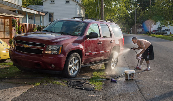 200901 Enterprise<br /> James Neiss/staff photographer <br /> Lockport, NY - Delmin Molina said he would much rather be outside after dinner washing his car in front of his Van Buren Street home than watching all the craziness on the evening news.