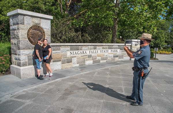 200714 State Park 3<br /> James Neiss/staff photographer <br /> Niagara Falls, NY - New York State Parks Police Sgt. Jeffrey Eckert snaps a photo for couple Omar Ramos and Jalisa Cruz who were visiting from Rochester. The wall behind is part of the Niagara Falls State Park Welcome Plaza $6.2 million revitalization project.