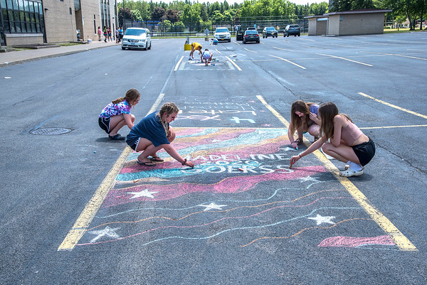 James Neiss/staff photographer <br /> Lockport, NY - Seniors at Lockport High School chalk draw a message in their parking spaces. Here, Madeline Goerss, second from left, gets help from friend Shannon Bull, sister Sydney Goerss and friend Sienna Marren, right.