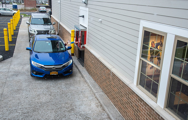 201215 Lewiston Hortons 2<br /> James Neiss/staff photographer <br /> Lewiston, NY - A poster of Tim Horton can be seen as customers get their drive-thru orders at the new Lewiston Tim Hortons on Center Street.