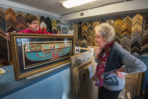 James Neiss/staff photographer <br /> Niagara Falls, NY - Sue Sullivan of Sue's Frame Of Mind on Center Street in Lewiston shows off her handiwork to customer Patricia O'Connor of the Town of Niagara who stopped in to pick up the artwork she purchased in Egypt. Sue's Frame Of Mind is celebrating 10 years in business on the Lewiston Center Street strip.