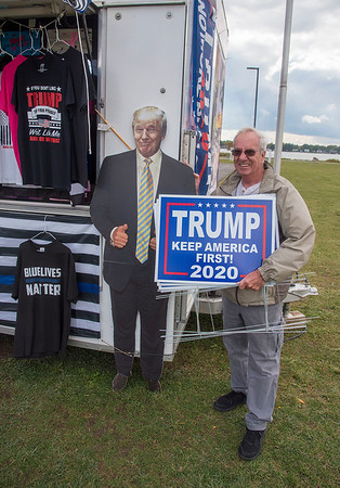 "201002 Trump Trailer 1<br /> James Neiss/staff photographer <br /> Niagara Falls, NY - Harry Byron of Wheatfield happily poses with a cardboard cutout of Donald Trump after picking up some campaign signs for his yard. A steady stream of customers visited the Trump trailer at Gratwick Riverside Park on Friday. When asked about the President contracting COVID-19 Byron said, ""Things can happen. I hope he gets better soon and I'll be praying for him, just like the country ought to be."""