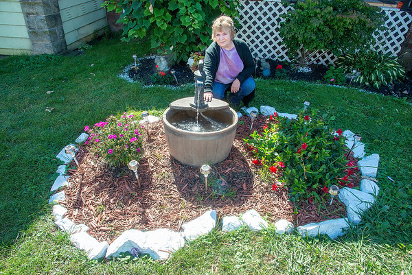200918 Wishing Well 1<br /> James Neiss/staff photographer <br /> Niagara Falls, NY - Tammy Lasut-Cuillo of Weston Avenue has been quietly granting wishes to neighborhood kids that have been tossing coins into her front yard fountain and making wishes.