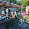 200730 Enterprise 3<br /> James Neiss/staff photographer <br /> Wilson, NY - Belle Muck, 11, brings flowers from her mother's garden to stock the shelves of their neighbors Bluebird Creek Vegetable Stand, owned by the Kam family on Wilson-Youngstown Road in Wilson. The Kam family keeps the booth filled with fresh vegetables, birdhouses made by Ron Kam, camp firewood and now, fresh flowers provided by the Muck's.