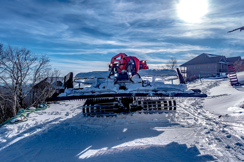 snow grooming machine parked on top of ski mountain