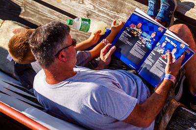 Race fans reading a Lucas Oil Late Model Dirt Series program