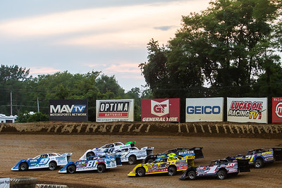 Cars pass in front of Lucas Oil Late Model Dirt Series billboards