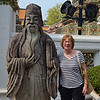 Anne with a statue in Wat Pho courtyard
