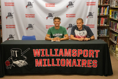 Trey Eiswerth sits with Coach Jeremy Steppe as he signs to do track and field at Point Park University.