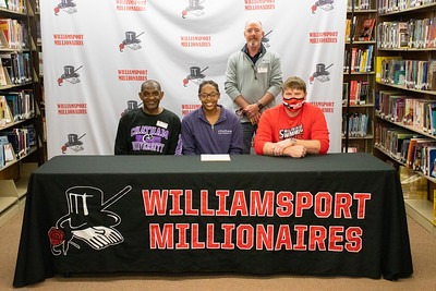Amy Jarvis sits with her father, Dr. Wingrove Jarvis, and coaches Jeff Beattie, standing, and Brett Johnson as she signs with Chatham University for swimming.