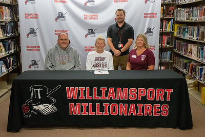 Jayla Bartholomew, center, signs with Bloomsburg University to play softball in the company of her parents, Brion and Shawna, and Coach Chase Smith.