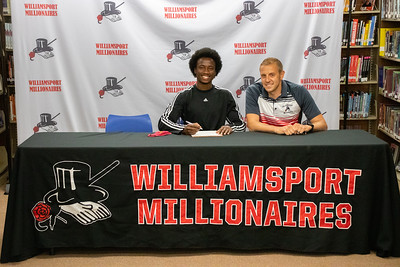 Shaheem Hill sits with Coach Jeremy Steppe as he signs his letter of intent to do track and field at Bloomsburg University.