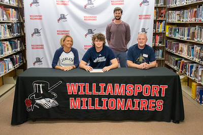 Derek Gehr, center, signs with Juniata College to play baseball in the company of his parents, Jonathan and Shelly, and Coach Kyle Schneider.