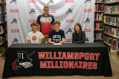 J. Henry Lyon, center, signs his letter of intent to do track and field at Penn State University in the company of Coach Jeremy Steppe, standing, and mother, Melinda, and friend, Patrick Nardi.
