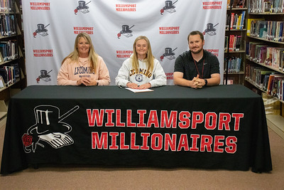Jackie Snyder, center, signs her letter of intent to play softball at Lycoming College alongside her mother, Lisa, and Coach Chase Smith.