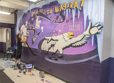 210920 NU Mural Enterprise James Neiss/staff photographer  Lewiston, NY - Buffalo artist Alessandra Price, of the AliWay Creative Agency, paints a mural on a wall between ice rinks at Niagara University's Dwyer Arena.