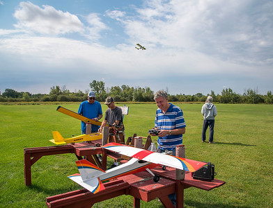 210913 Plane Enterprise James Neiss/staff photographer  Lockport, NY - Flying Weather - Ken Lee flys his RC plane in the background at the Niagara County Model Plane Field on Day Road as enthusiasts Clarence Ragland, Rich Smyth and Carl Cascia work on planes.