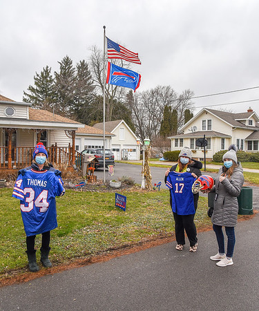 210112 Bills Fans 1<br /> James Neiss/staff photographer <br /> Newfane, NY - Bills Fans Dawn James, left and daughter Lauren James, right, both of Lockport, were walking by and volunteered to hold Buffalo Bills memorabilia weighing down rabid fan Katie Grace, center. She and her boyfriend Nick Polley decorated their Grace Avenue home together.
