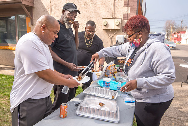 210409 W.A.W.G. 4 James Neiss/staff photographer  Niagara Falls, NY - Volunteer cook Ashlee Vanderberg serves up BBQ Chicken Wings for Eric Jones, Christopher Freeney and Antoine White at the Entrepreneur School of Thoughts gathering on 19th Street.