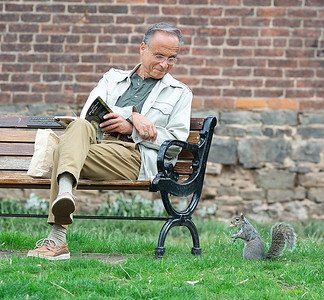 210409 Enterprise 1B James Neiss/staff photographer  Lewiston, NY - Harmony with Self & Nature - Burt Fattta enjoys a peaceful afternoon at Hennepin Park in Lewiston studying a book titled The Buddha Eye and making friends with the squirrels, sharing his bag of peanuts.