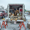 210220 Winter Markets 1<br /> (James Neiss/staff photographer)<br /> North Tonawanda, NY - Three generations of the family owned Berry Farms in Pendleton, Scott Berry, Lucas Berry, 11 and his father Jonathan Berry warm themselves with a propane heater in the back of their farm truck as they wait for customers at the North Tonawanda Farmers' Market.