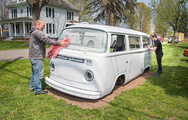 """210427 Enterprise 3A<br /> James Neiss/staff photographer <br /> Pendleton, NY - Ella Goudy, 15, gets help from her father Eric turning an old Volkwagon van into a vegetable stand in front of their Irish Road home. The family plans to call their stand """"VW Homestead"""" and sell vegetables, fresh eggs, fruit and wildflowers."""