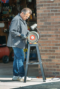 210409 Enterprise 2 James Neiss/staff photographer  Town of Niagara, NY - Sparks shower all around Leo Lester as he concentrates on sharpening his lawn mower blades. Many lawns will be cut for the first time this Saturday as warm temperatures and sunny skies are expected.