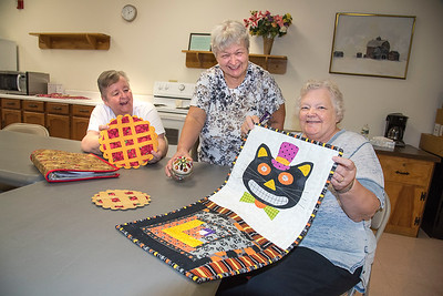 210922  Quilters Enterprise James Neiss/staff photographer  Lockport, NY - Quilter Bea Zanow of Gasport, right, holds her quilted Halloween wall hanging as Debby Plump of Lockport helps show off Zanow's quilted trivets. At Center, Alice Donaldson of Clarence, shows off her wool applique pincushion during a meeting of the quilting clup at the Dale Association. New members are alway welcom.