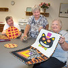 210922  Quilters Enterprise<br /> James Neiss/staff photographer <br /> Lockport, NY - Quilter Bea Zanow of Gasport, right, holds her quilted Halloween wall hanging as Debby Plump of Lockport helps show off Zanow's quilted trivets. At Center, Alice Donaldson of Clarence, shows off her wool applique pincushion during a meeting of the quilting clup at the Dale Association. New members are alway welcom.