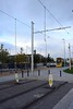 Earthing straps on the OCS at Broombridge. A tram replacement bus is waiting at the bus stop. Sun 26.09.21