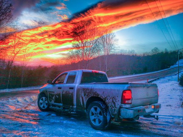pickup truck and fiery sunset sky during winter
