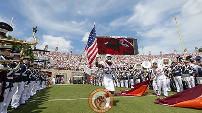 Armani Chatman runs onto the field with the American flag. (Mark Umansky/TheKeyPlay.com)