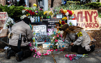 8  Brown Berets begin to place a cross made of flowers at the shrine