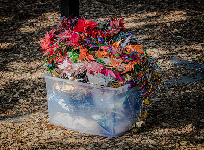 2  1,000 peace cranes (origamis), rubberized for protection from the weather, await to be hung from the gate