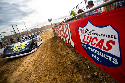 Matt Cosner driving by a Lucas Oil Products banner