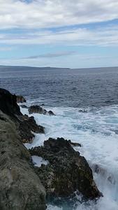 The rocky coastline and powerfully crashing waves.