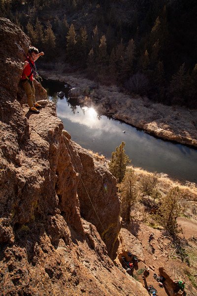 """Wes at the anchor ledge on """"9999"""" (5.6) at the Waterfall Slab with the Crooked River reflection sun below."""